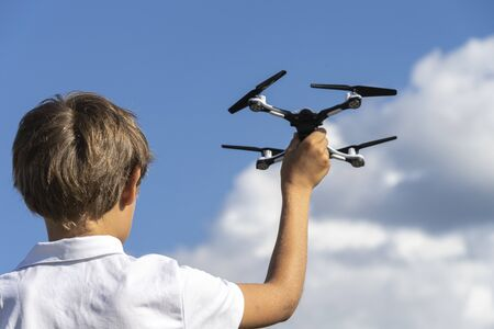 Boy playing with drone in summer day outdoors against blue sky