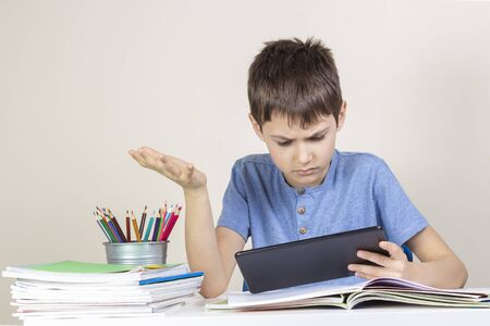 Confused,surprised child with tablet computer sitting at table with books notebooks Imagens