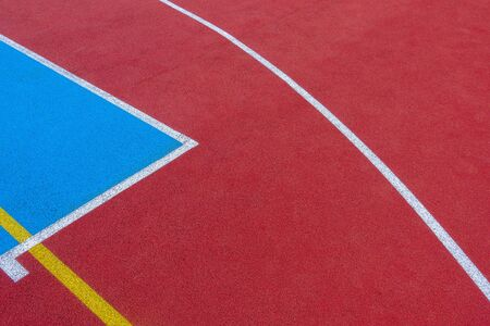 Colorful sports court background. Top view to red and blue field rubber ground with white and yellow lines outdoors 写真素材