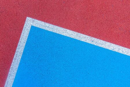 Colorful sports court background. Top view to red and blue field rubber ground with white lines outdoors