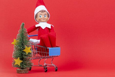 Christmas shopping concept. Funny toy elf sitting in mini shopping cart and little Christmas tree on red background