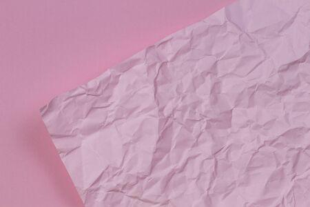 Pink crumpled wrinkled paper over blank pink paper texture background Banco de Imagens