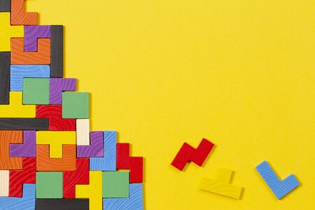 Different colorful shapes wooden blocks on yellow background. Top view