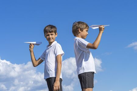 Two boys holding white paper planes against blue sky