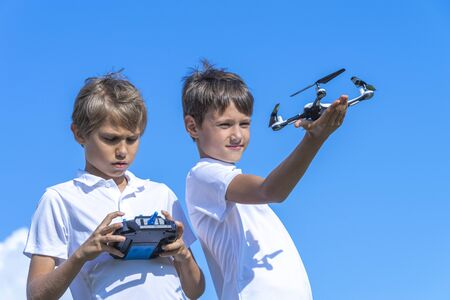 Boys playing with drone in summer day outdoors against blue sky