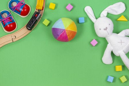 Baby kids toys background with toys train, colorful wooden blocks and soft plush toys on light green background. Top view, flat lay 版權商用圖片