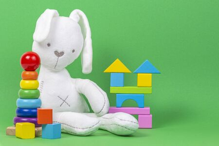 White plush toy rabbit, baby stacking rings pyramid and colorful wooden blocks on light green background 版權商用圖片 - 128764724
