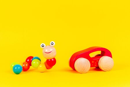 Wooden kid toys background. Colorful baby toy worm and wooden car on yellow background Reklamní fotografie