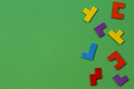 Different colorful shapes wooden blocks on green background. Top view Stock Photo