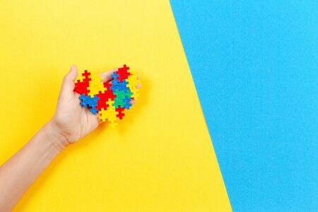 Child hand holding colorful heart on yellow and blue background. World autism awareness day concept