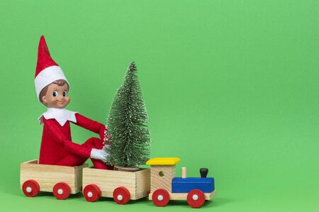 Christmas background. Wooden toy train with sitting toy elf and small Xmas fir tree on light green background