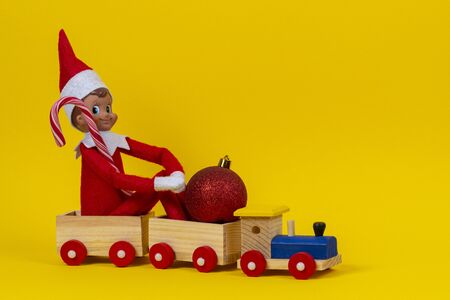 Christmas background. Wooden toy train with sitting toy elf dwarf, candy can and red Xmas bauble on yellow background