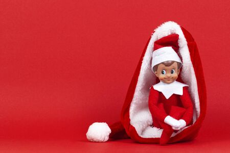Little smiling Christmas toy elf sitting in Santa hat on red background