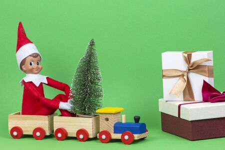 Christmas background. Wooden toy train with sitting toy elf and small Xmas fir tree, present boxes on light green background