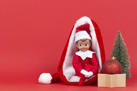 Little smiling Christmas toy elf sitting in Santa hat with little Christmas fir tree and Xmas bauble and present box on red background Stockfoto
