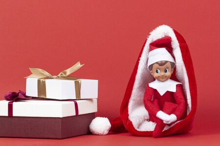 Little smiling Christmas toy elf sitting in Santa hat with Xmas presents boxes on red background Stockfoto