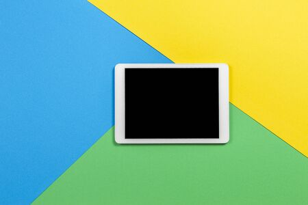 Digital tablet computer on light blue, green and yellow background. Top view 版權商用圖片