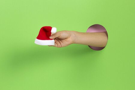 Hand through hole in light green background holding small red Christmas Santa Claus hat Stockfoto