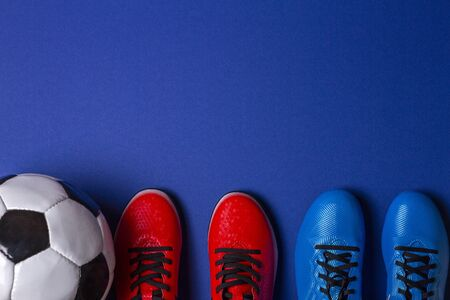 Top view of soccer ball and two pairs of soccer football sports shoes on blue background