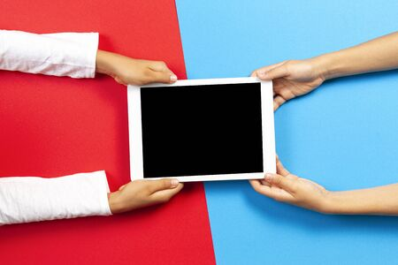 Kids holding tablet computer over red and light blue background