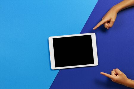 Kid hands pointing fingers to blank tablet computer on blue background 写真素材
