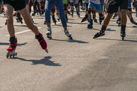 Many legs in roller-blades. People participate in outdoors racing marathon