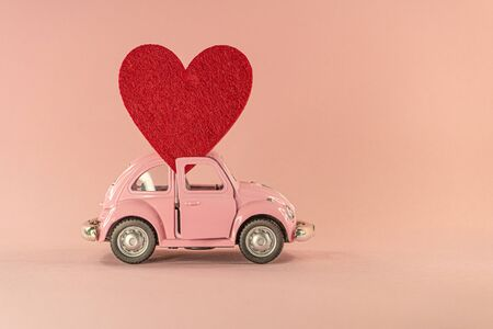 Little retro toy model car with red heart on pastel pink background. Love, friendship, valentines day, delivery, donation concept