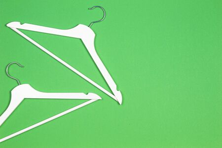 Two white wooden hangers on pastel green background. Shopping, sale, promo, social media, new season concept Stockfoto - 130732296