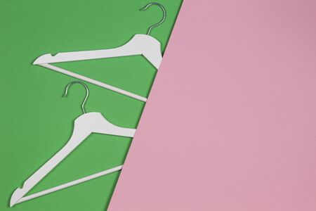 Two white wooden hangers on pastel pink and green background. Shopping, sale, promo, social media, new season concept