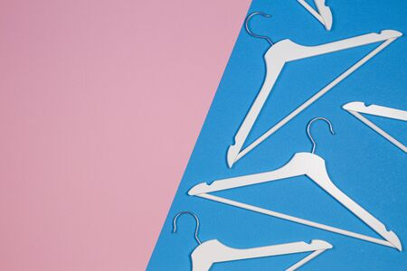 White wooden clothes hangers on pastel pink and blue background. Shopping, sale, promo, social media, new season concept Stockfoto - 130732307