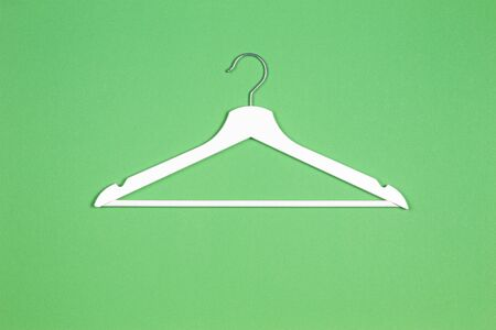One white wooden hanger on pastel green background. Shopping, sale, promo, social media, new season concept 스톡 콘텐츠