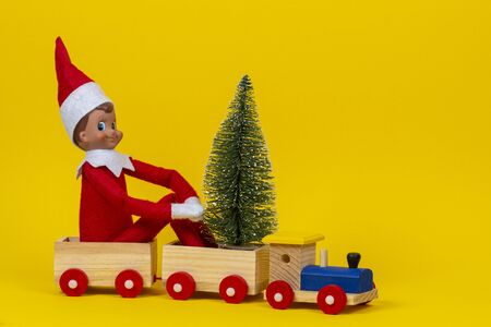 Christmas background. Wooden toy train with sitting toy elf dwarf and small Christmas tree on yellow background Zdjęcie Seryjne - 130732471