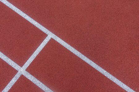Fondo colorido de la cancha de deportes. Vista superior al suelo de caucho de campo rojo con líneas blancas al aire libre Foto de archivo