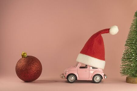 Pink retro toy model car with small red Christmas Santa Claus hat, little Xmas fir tree and red bauble on pastel pink background