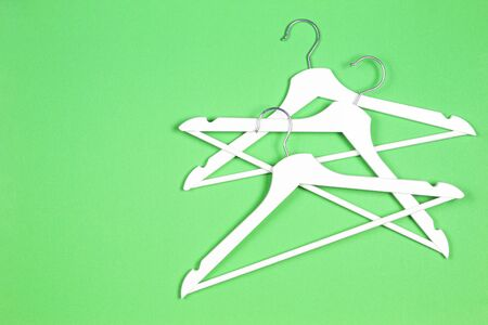 White wooden hangers on pastel green background. Shopping, sale, promo, social media, new season concept