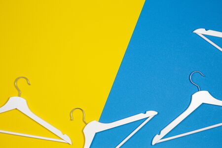 Two white wooden clothes hangers on yellow and light blue background. Shopping, sale, promo, social media, new season concept