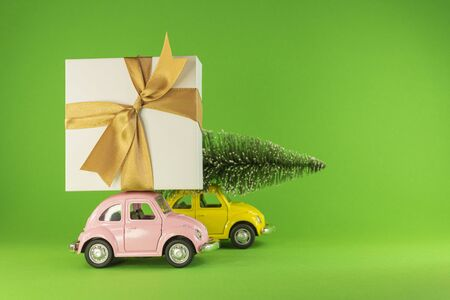 Vilnius, Lithuania - September 09, 2019: Little retro toy model cars with present gift box and small Christmas tree on green background