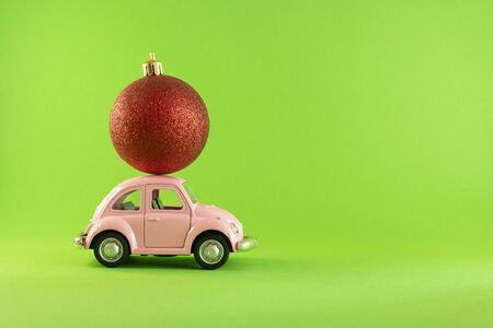 Vilnius, Lithuania - September 09, 2019: Pink retro toy model car with small red Christmas tree decoration bauble on green background