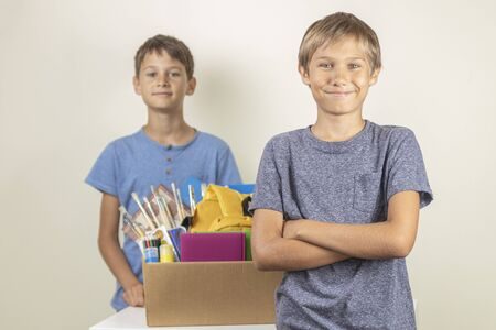 Donation concept. Kids happy to help others. Boys with donation box with books and school supplies