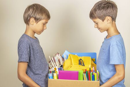 Donation concept. Kids holding donate box with books and school supplies Stock Photo