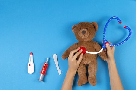 Kid hands play with toy stethoscope, teddy bear and toy medicine tools on light blue background. Top view