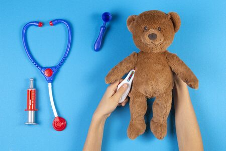 Kid hands measuring temperature with toy thermometer of teddy bear, toys medicine tools on light blue background. Top view Stock Photo