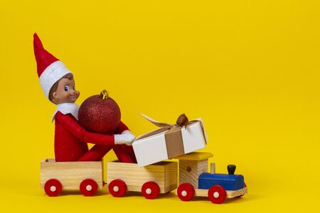 Christmas background. Wooden toy train with sitting toy elf dwarf, present gift box and red Xmas bauble on yellow background