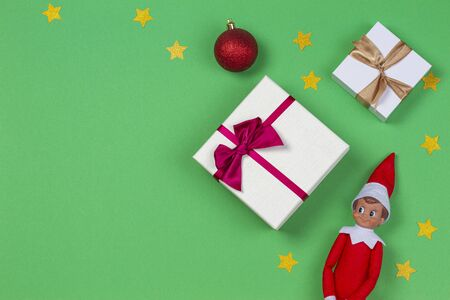 Christmas background. Toy elf, white present boxes and Xmas decoration bauble on light green background with golden stars.