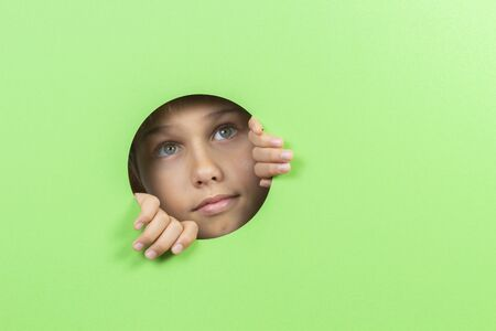 Kid watching through hole in green color background