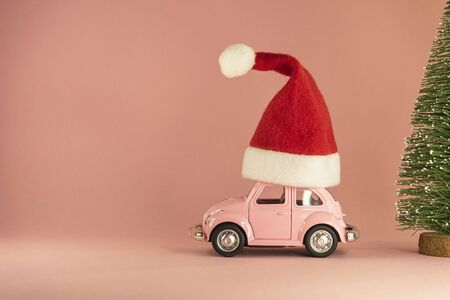 Pink retro toy model car with small red Christmas Santa Claus hat and little Xmas tree on pastel pink background