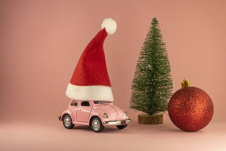 Pink retro toy model car with small red Christmas Santa Claus hat and little Xmas tree, red bauble on pastel pink background