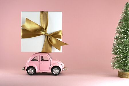 Vilnius, Lithuania - September 09, 2019: Little retro toy model car with present gift box and little Xmas tree on pastel pink background