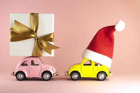 Christmas background. Little retro toy model car with Santa Claus hat and pink model car with present gift box on pastel pink background. Vilnius, Lithuania, September 09, 2019