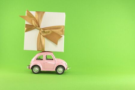 Little retro toy model car with present gift box on light green background. Christmas, birthday, valentines day, delivery concept